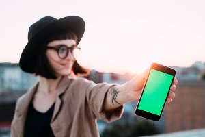 Cute hipster girl with mockup phone