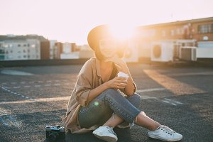 Cute girl sits on sunny rooftop