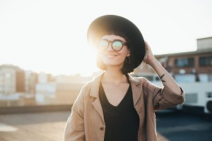 Fashion trendy woman poses in sun