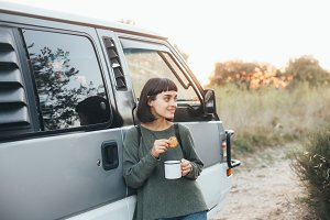 Cute girl snacks with coffee at camp