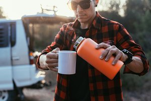 Man pours hot coffee from thermos