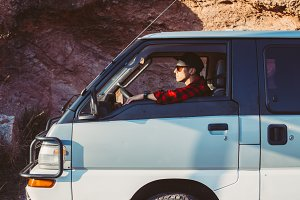 Man sits in van during road trip