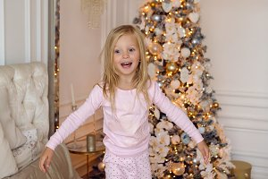 girl in pink pajamas having fun on a large bed on Christmas day