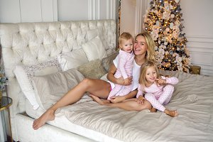 mother with two daughters in their pajamas sitting on the bed