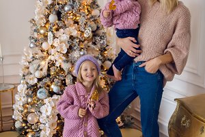 mother with two daughters standing by the Christmas tree in a sweater