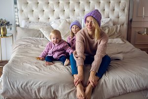 mother with two daughters sitting on the bed in a sweater