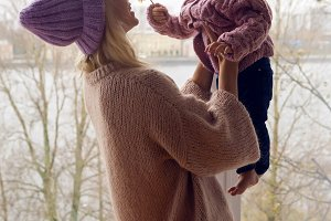 mother holding daughter at the window dressed