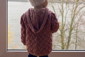 little girl in a purple sweater and cap standing at the window