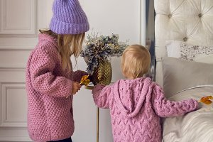 two sisters in sweaters and hat are back at home