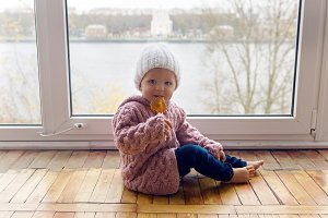 little girl in a purple sweater and cap sitting