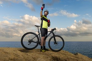 Mountain biker takes picture on clif