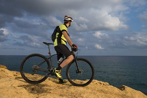mountain biker looks at the sea from