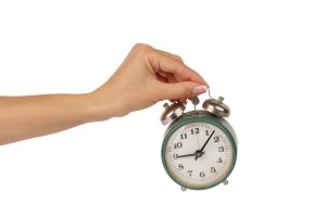 Alarm clock in the woman's hand, isolated