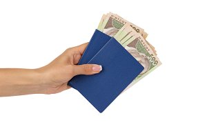 Woman's hand holds passports with banknotes of five hundred hryvnias, isolated