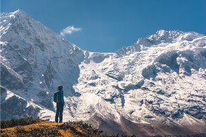 Standing young woman on the hill and looking on amazing Himalaya