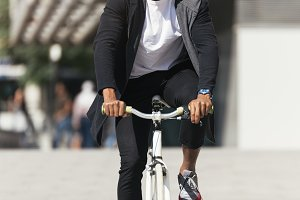 Handsome afro man riding a bike.