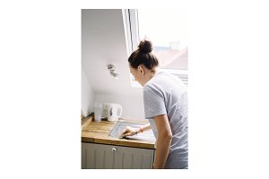 Young woman do cleaning in kitchen