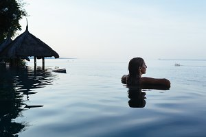 Girl relaxing in infinity pool