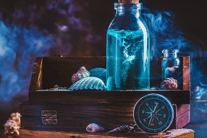 Glass bottle with trapped tornado swirl inside. Marine still life with compass, seashells and travel essentials.