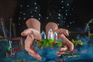 Young witch holding a floating turf with moss and crystals. Mystical scene with smoke and magical supplies.