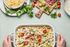 Female hands holding pasta casserole