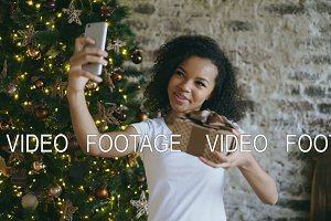 Curly teenage girl chatting online conversation using smartphone camera at home near Christmas tree