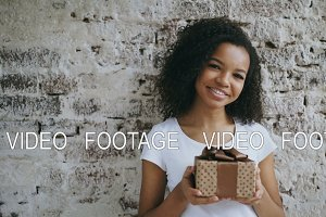 Portrait of young african american woman holding gift box and smiling into camera
