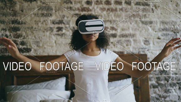 Young mixed race girl getting experience using VR 360 headset glasses of virtual reality at home