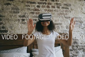 Young african woman getting experience using VR 360 headset glasses of virtual reality at home