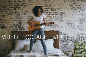 Mixed race young funny girl playing acoustic guitar and have fun dancing on bed at home