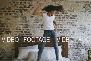 Curly mixed race young joyful girl have fun dancing on bed at home