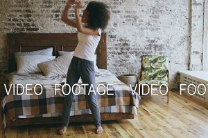 Attractive mixed race joyful girl have fun dancing near bed at home