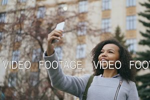 Cheerful african american student girl talking at video call with smartphone near univercity