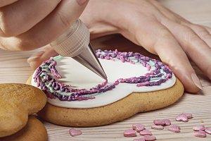 Confectioner decorates cookies.