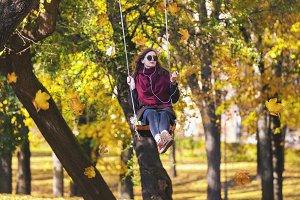 Teenage girl swinging in autumn park