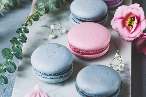 Pastel macaroons, cupcakes and flowers on marble background.