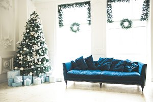 Christmas living room with a Christmas tree, sofa, gifts and a large window. Beautiful New Year decorated classic home interior
