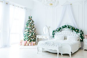 Christmas living room with a Christmas, gifts tree and bed. Beautiful New Year decorated classic home interior. Winter background