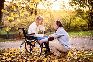 Senior couple in wheelchair in autumn nature.