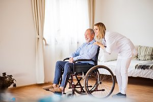 Nurse and senior man in wheelchair during home visit.