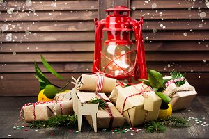 Many decorated Christmas presents and old vintage oil lamp on wooden background