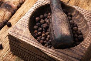 peppercorn in retro wooden mortar