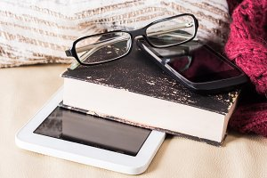 Glasses, book and gadgets on leather sofa