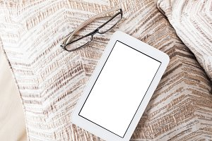 Glasses and white tablet on a pillow