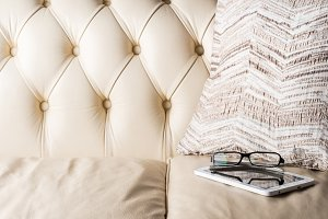 Glasses and white tablet on leather sofa