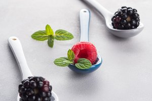 Fresh berries on spoons on gray background