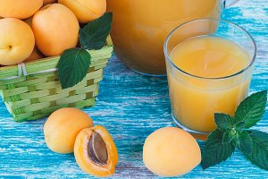 Ripe orange apricots in the basket with leaves of mint and glass of juice