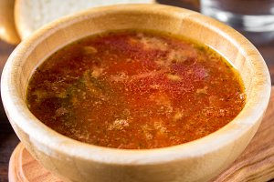 Traditional Ukrainian Russian vegetable borscht on the old wooden background.