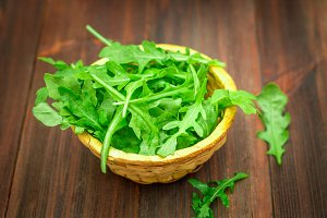 Fresh juicy leaves of arugula on a brown wooden table.