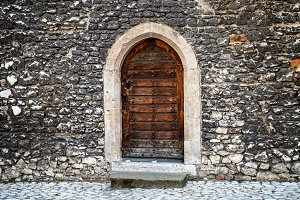 Old wooden door with stone wall